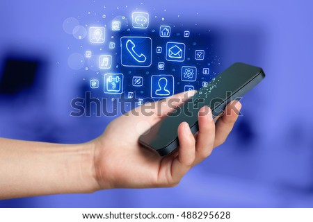 Hand holding smartphone with glowing mobile app icons #488295628