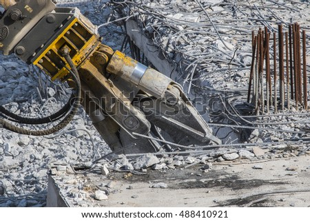 Close up of building demolition by excavator arm. Demolition of houses by hydraulic crashers.  Royalty-Free Stock Photo #488410921