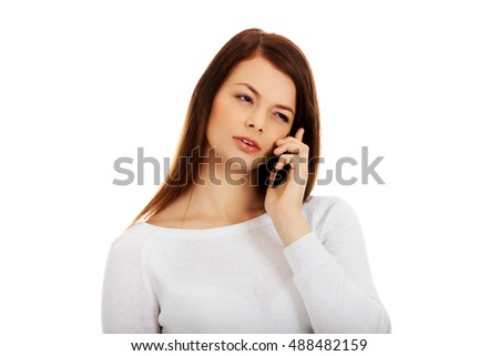 Thoughtful teen woman talking through a mobile phone #488482159