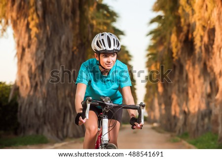 Portrait of happy smiling young female cyclist riding bike on road with palms in sunset. Nature, healthy and active lifestyle concept #488541691