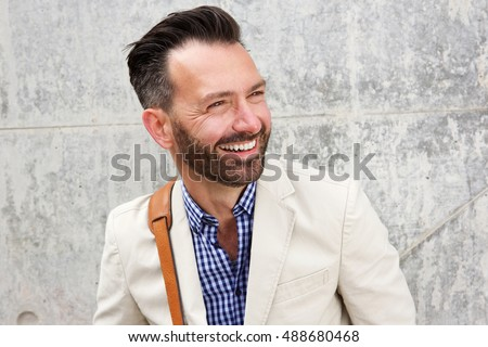 Close up portrait of cheerful middle aged man with beard standing against wall and smiling #488680468