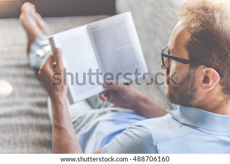 Back view of handsome young businessman in casual clothes and eyeglasses reading a book while lying on couch at home #488706160