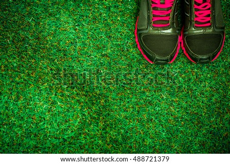 sports shoes and equipment on the background of green grass #488721379