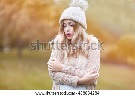 Beautiful young blonde woman wearing knitted sweater and hat. Cold fall and winter concept #488834284