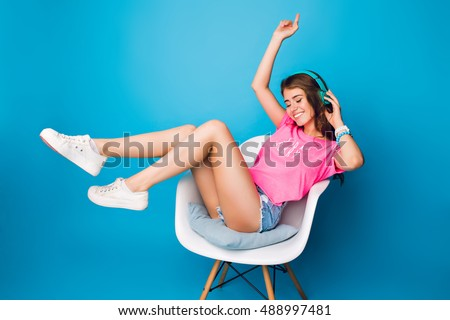 Pretty girl with long curly hair  listening to music in chair on blue background in studio. She wears shorts, pink T-shirt, white sneakers. She holds legs above and keeps eyes closed.