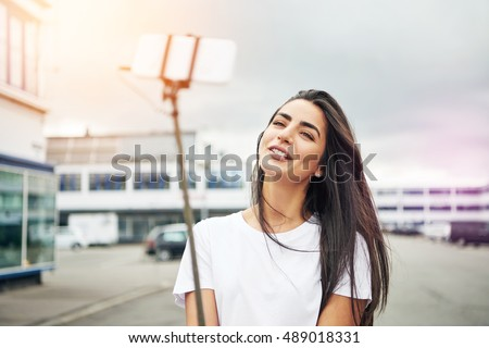 Pretty young adult woman in white blouse smiling for camera on selfie stick while standing in street on cloudy and windy day