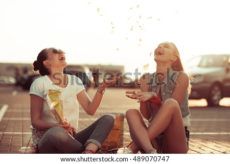 Girls have fun in parking with drinks at the sunset