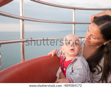 Young mother with her toddler son playing outdoors on Ferris wheel #489084172