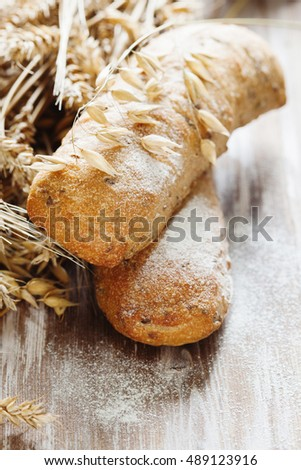 Wholegrain bread with seeds, rye and wheat spikelets on a rustic wooden board #489123916