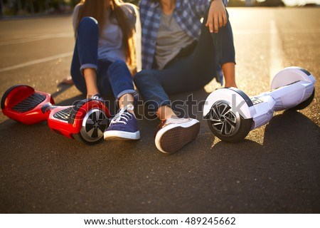 young man and woman riding on the Hoverboard in the park. content technologies. a new movement. Close Up of Dual Wheel Self Balancing Electric Skateboard Smart   #489245662