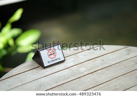 No smoking sign on wood table in the garden at hotel.