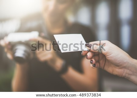 Closeup of instant photo in the hands of women. Blank white business card in female hands.Ring on a finger.In the background is blurred woman holding an instant camera.Film effect,blurred background.
