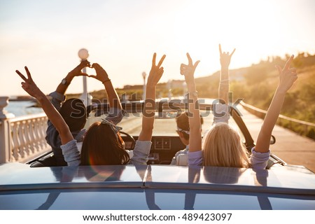 Group of happy young friends in cabriolet with raised hands driving on sunset #489423097