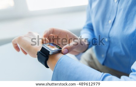 business, technology, communication and people concept - close up of woman hands with incoming call on smart watch screen at office #489612979