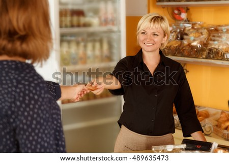 Accepting credit cards. Shot of a female customer paying for her purchase with a credit card at the local bakery