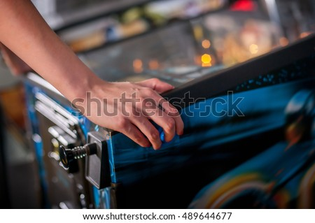 Hand of female pressing button and playing pinball machine Royalty-Free Stock Photo #489644677