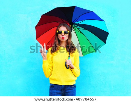 Fashion pretty cool woman holding colorful umbrella in autumn day over blue background wearing yellow knitted sweater #489784657