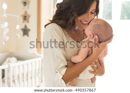 Young mother holding her baby in the bedroom Royalty-Free Stock Photo #490357867