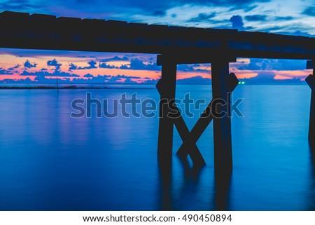 Wooden bridge at sunset at sea #490450894