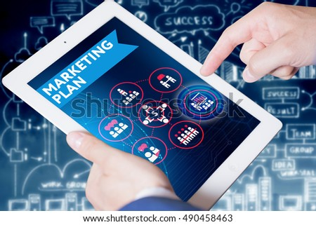 Business, Technology, Internet and network concept. Young businessman, working on the tablet , select on the virtual display: Marketing plan
