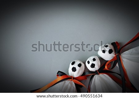 Halloween concept background : Three halloween ghosts DIY made from white tissue paper, black and orange ribbon on gray background  #490551634