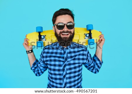 Young hipster bearded man with a yellow skateboard and sunglasses smiling on blue background #490567201
