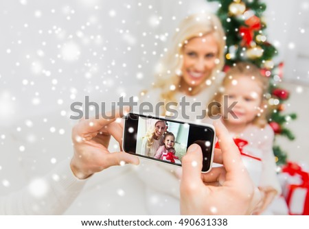 family, christmas, technology and people concept - close up of man taking picture of his family by smatrphone #490631338