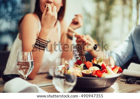young girl sitting in the courtyard of restaurants and eating juicy fruits #490947355
