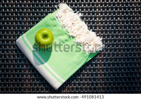 The concept of a flat lay summer accessories close-up of a white and green Turkish peshtemal / towel and green apple on a rattan lounger. #491081413