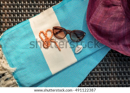 The Concept of flat lay summer accessories of white turquoise color Turkish towel / peshtemal, sunglasses, seashell, orange necklace and crimson / redviolet color straw hat on rattan lounger . #491122387