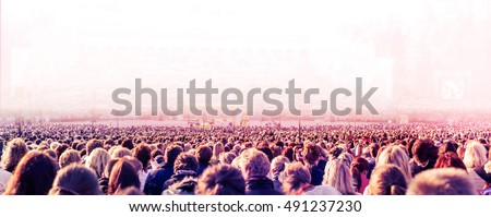 Panoramic photo of large crowd of unrecognizable people. Slow shutter speed with motion blur. #491237230