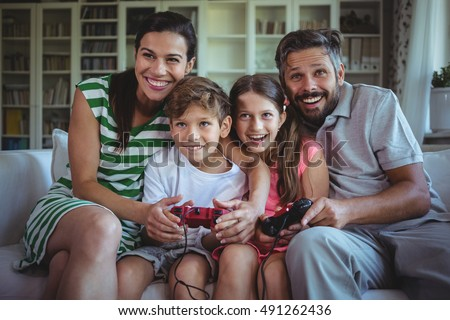 Parents sitting on sofa with their children and playing video games at home #491262436