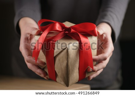 female teen girl shows paper gift box with red ribbon and a bow #491266849