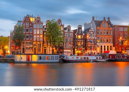 Amsterdam canal Amstel with typical dutch houses and boats during twilight blue hour, Holland, Netherlands. #491271817