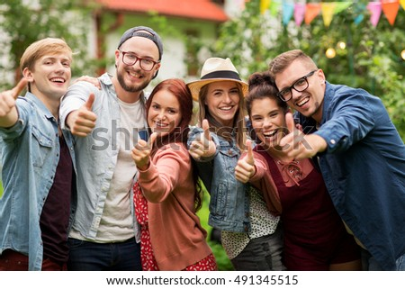 leisure, holidays, reunion, people and friendship concept - happy teenage friends showing thumbs up at summer garden party #491345515