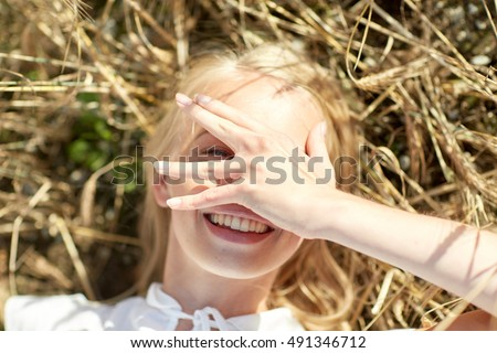 nature, summer holidays, vacation and people concept - close up of happy young woman lying on cereal field and covering face by hand #491346712