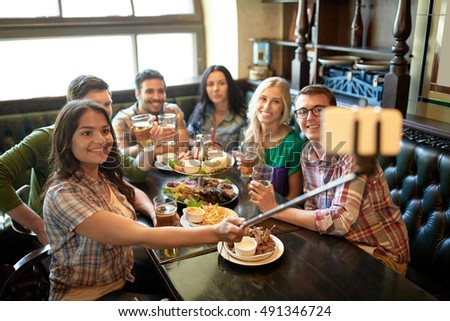 people, leisure, friendship and technology concept - happy friends taking picture by smartphone selfie stick, drinking beer and eating snacks at bar or pub #491346724
