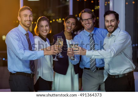 Portrait of businesspeople toasting glasses of champagne in office at night #491364373