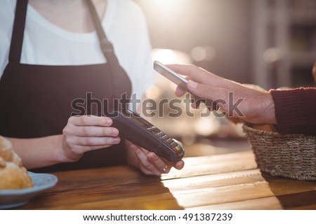 Customer paying bill through smartphone using NFC technology in cafe #491387239