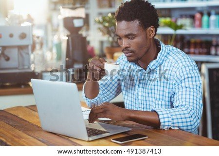 Man using a laptop while having cup of coffee in cafe #491387413