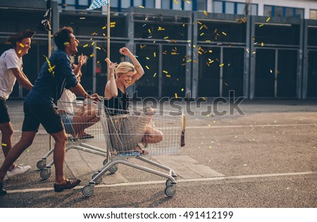 Multiethnic young people racing with shopping cart and blowing confetti. Young friends having fun on shopping carts. Royalty-Free Stock Photo #491412199