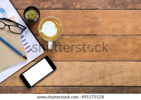 Office stuff with blank screen smart phone,  leather notebook, glasses, pencil, graph or analysis chart and cup of coffee. Top view with copy space.Office desk table concept. #491575528