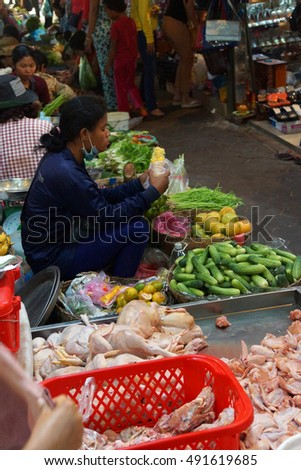 SIEM REAP, CAMBODIA - FEB 16, 2015 - Woman selling vegetables in the market of  Siem Reap,  Cambodia #491619685