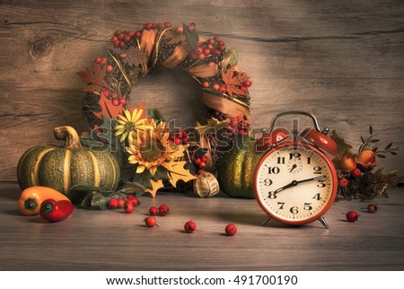 Fall still life with vintage alarm clock, ornate wreath with berries and ribbons. Design for your Thanksgiving, birthday or anniversary greeting. This image is toned. Focus on the clock.