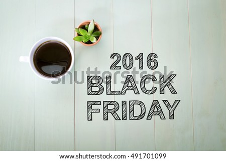 Black Friday 2016 text with a cup of coffee on pastel green wooden table #491701099