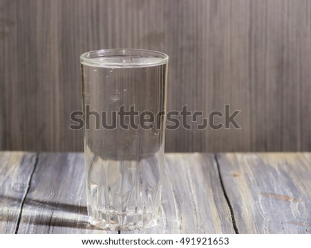 A glass of water on wooden background with backlight #491921653
