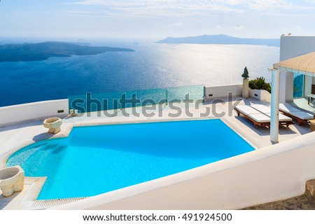 View of caldera and swimming pool in foreground, typical white architecture of Imerovigli village on Santorini island, Greece #491924500