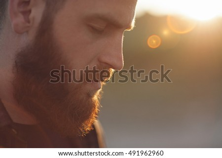 young bearded man with closed eyes on the background of the sun's rays #491962960