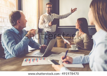 Business people are working in office. Handsome young businessman is making presentation for his colleagues, using a digital tablet and pointing to the board
