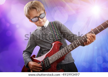 Boy playing electric guitar on stage in rock music school talent show #491993497